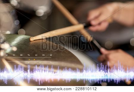 music, people, musical instruments and technology concept - close up of musician with drumsticks playing drum kit at concert at sound recording studio