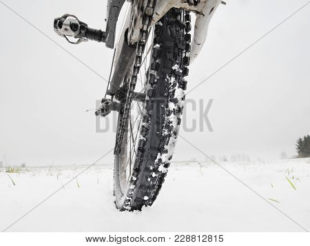 Close-up Of The Rear Wheel Of Mountain Bicycle In Snowy Meadow In The Countryside. Detail Of The Mou