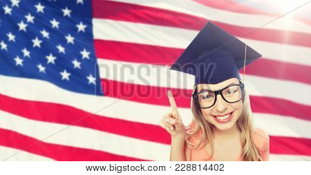 people, graduation and national education concept - smiling young student woman in mortarboard and eyeglasses pointing finger up over american flag background