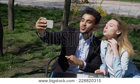 Siblings Looking At Phone S Screen, Man Leaf Photos. Lady Has Beautiful Long Hair And Dressed In Den