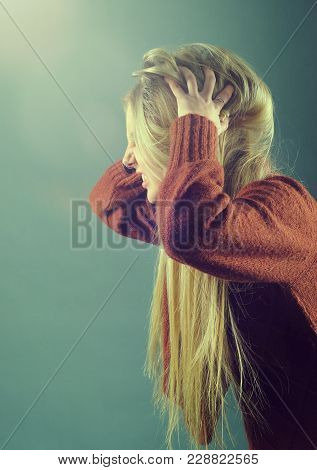 Young Blond Girl Furiously Scratches Her Tangled Hair