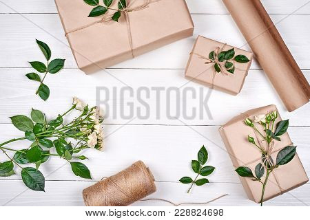 Gift Wrapping Background. Rolls Of Kraft Wrapping Paper, Twine, Branch Of Roses, Gift Boxes On Woode