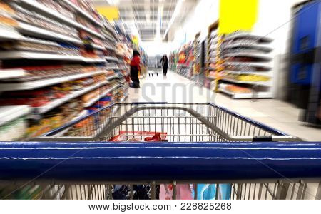 Grocery Shopping Trolley Close Up In Supermarket Aisle