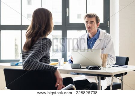 High angle view of a young physician listening to his patient with respect and dedication, during a private consultation in the office of a modern medical center