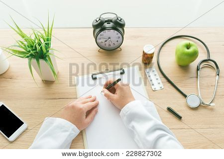 Female Doctor Writing Notes On Clipboard Paper During Medical Exam