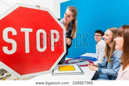 Driving teacher explaining meaning of street signs to class of students