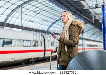 Woman in train station using time table app on phone while a modern train is approaching