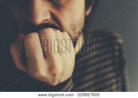 Nervous Man Bites Fingernails,low Key Close Up With Selective Focus