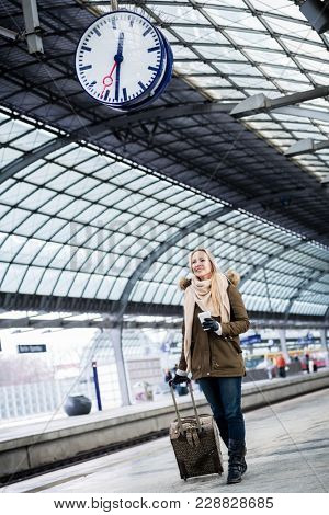 Woman looking impassionate at clock in train station as her train has a delay