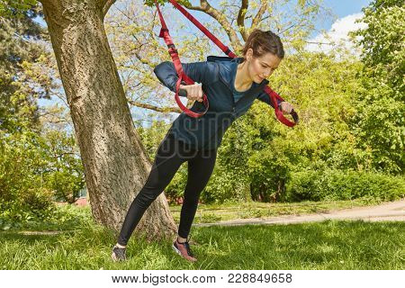 Woman sling training or suspension training at park