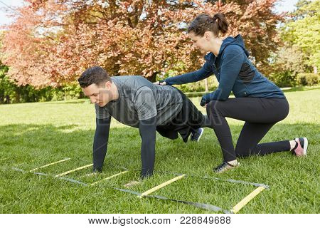 Woman trains man as Personal Trainer in the park