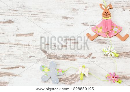 Easter Bunny With Flowers On Bright Wooden Background