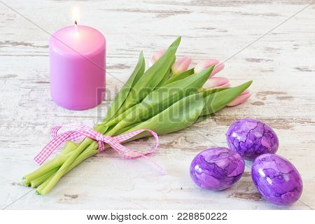 Bunch Of Pink Tulips With Candle And Easter Eggs On Rustic Wooden Background
