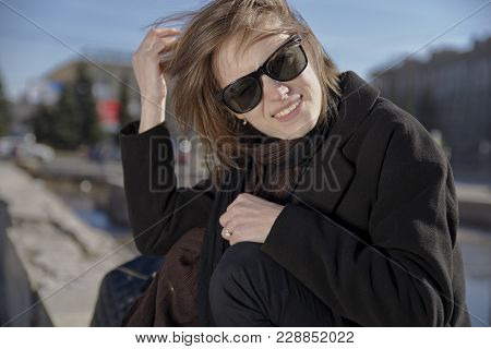 Smiling Young Woman In Sunglasses Black Coat And Scarf Smiling Wide With Teeth And Squinting From Th