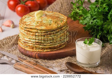 Many Pancakes With Fresh Herbs And Sour Cream Sauce On A Wooden Table. Traditional Ukrainian Or Russ