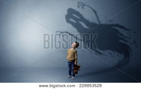 Scary ghost shadow in a dark empty room with a cute blond child