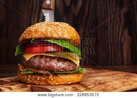 Tasty grilled home made burger with beef, tomato, cheese, cucumber and lettuce. With space for your recipe
