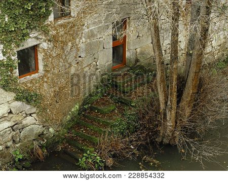 House Next To A River With A Tree In The Town Of Allariz, Galicia. Spain
