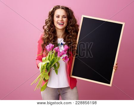 Smiling Young Woman With Bouquet Of Tulips Showing Black Board