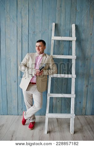 Handsome Man In Beige Suit And Pink Shirt With Microphone Against Ladder Background On Studio. Toast