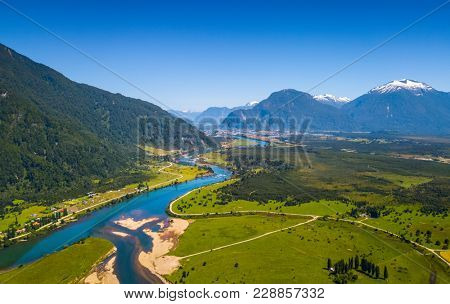 Aerial view of the green valley with river and mountains on the background. Area near the town of Puerto Aysen, Chile