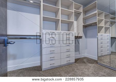 Large Walk-in Closet With White Shelves, Drawers