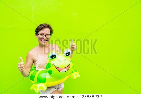 Young Woman With An Inflatable Circle Frog On A Green Wall Background Showing A Hand Gesture Thumb U