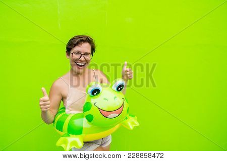 Young Woman With An Inflatable Circle Frog On The Background Of A Green Wall Fooling Around And Show
