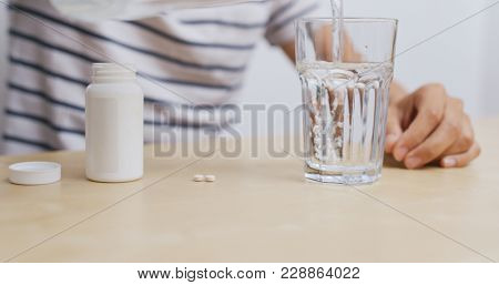 Man taking pill at home