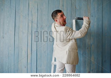 Handsome Man In Beige Suit And Pink Shirt With Microphone Against Ladder Background On Studio. Funny
