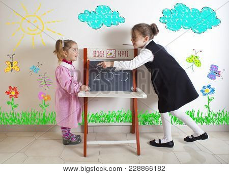 Little Girl Teaching Mathematics To A Younger Child Next To The Chalkboard