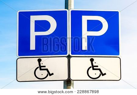 Double Road Sign Parking Place For The Disabled Against The Blue Sky. Handicapped Parking