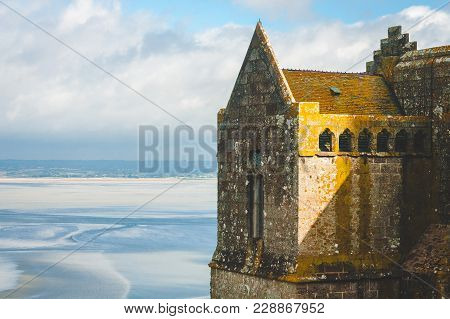 Close Up On Fragment Of Stone Abbey Covered With Moss On Le Mont Saint-michel Island During Low Tide