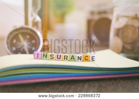 Medical And Health Care Management Concept Word Block Insurance On Yellow Book Over Wooden Backgroun