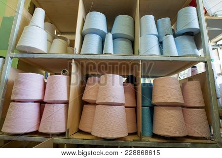Spools With Different Pastel Color Thread On Shelves At Knitting Factory Shot