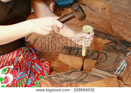 Woodcarving. An Employee With A Chisel And A Kyanik Carves Elements From A Tree For A Temple.