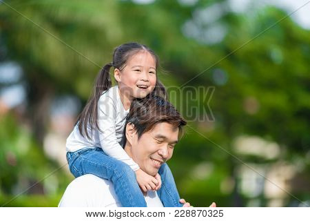 Cute Asian Girl On Neck Dad Big Happy Laughing And Run Around Together. Happy Man Piggybacking Adora