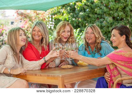 group of middle aged women drinking wine at party