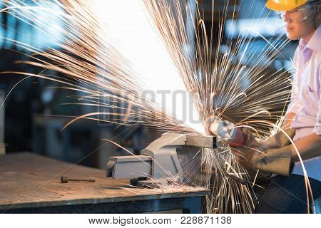 Selective Focus At Steel Rod And Motion Blurred. Man Use Electric Steel Cutter And Clamp Metal In Fa