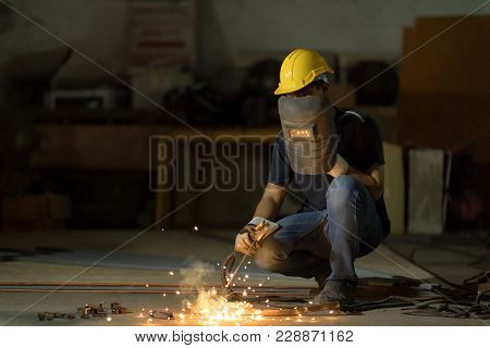Selective Focus At His Eye. Welder Or Craftsman In A Welding Mask And Welders Leathers, A Metal Prod