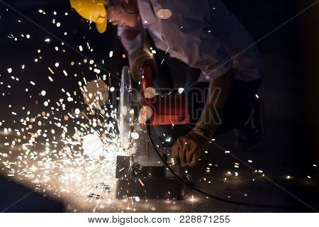 Low Light Image Of Worker Ware Yellow Helmet Kneel Use Electric Steel Cutter Machine. He Has A Hard
