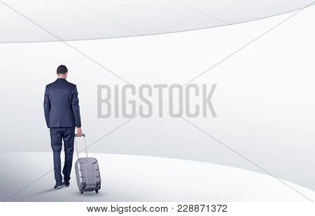 Businessman with back walking in a white waiting room with empty walls around