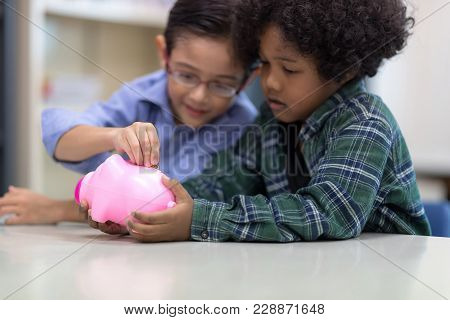 Selective Focus At Pig Jar. Kids Playing Collect Money With A Pink Saving Pig Jar In The Library. Se