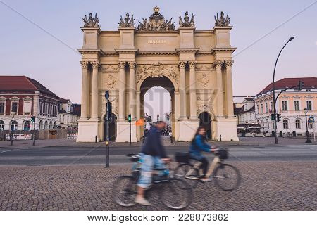 April, 9th, 2017 - Potsdam, Brandenburg, Germany. People Riding Bikes Near Brandenburg Gate On Potsd
