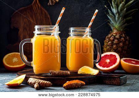 poster of Immune boosting, anti inflammatory smoothie with orange, pineapple, turmeric. Detox morning juice drink, clean eating