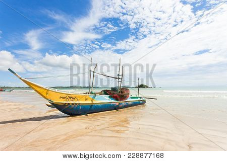 Weligama Beach, Sri Lanka, Asia - A Traditional Fishing Boat At The Sandy Beach Of Weligama