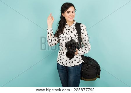 Portrait Of Young Attractive Woman Photographer In White Shirt Holding Camera And Bag Showing Ok Ges