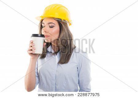 Pretty Female Constructor Smelling Takeaway Coffee.