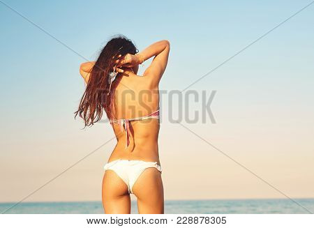 Beautiful Sexual Young Woman Stands On The Beach Against The Sea And Sky. Happy Woman Enjoys Summer