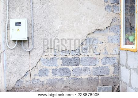 Destroyed Wall. Gray Plaster. Large Uneven Stones.